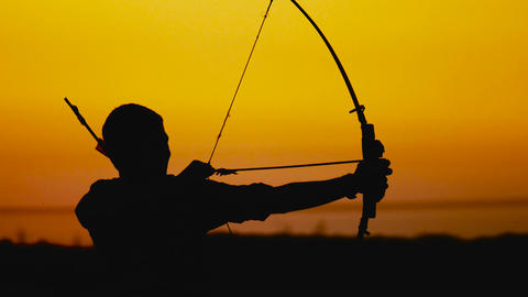 Archery silhouette, sun sets behind the archer GIF