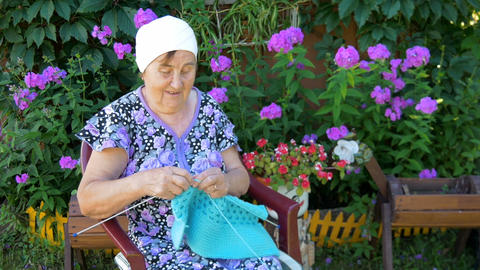 Elderly woman knitting sitting on the street outside his home Footage