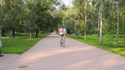 A man rides a bicycle in the park on a sunny day Footage