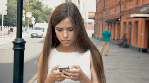 Beautiful girl walking on the city. Typing sms Live Action