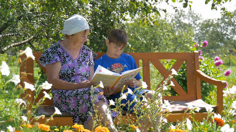 Grandson reading a book to his grandmother