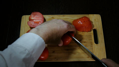 Chef cuts red tomatoes for salad Footage
