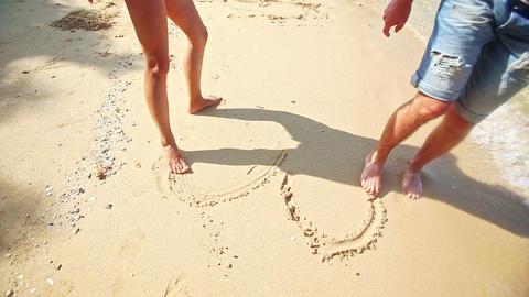 Girl Guy Feet Barefoot Draw Heart on Sand Beach at Wave Edge Footage