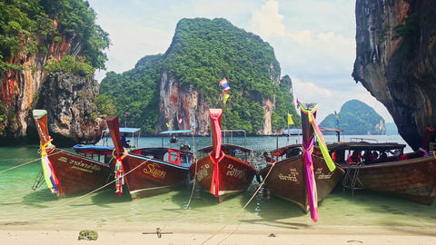 Thai Longtail Boats in Shallow Sea by Beach against Green Cliffs Footage