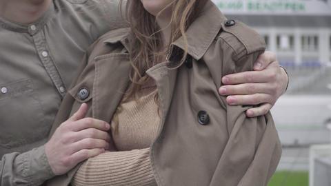 Unrecognizable young man covering brunette woman with coat. Boyfriend taking Acción en vivo