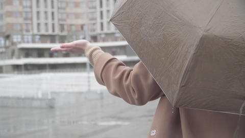 Back view close-up of unrecognizable Caucasian girl checking rain with hand Acción en vivo