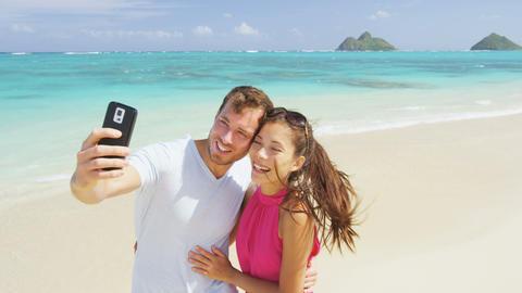 Couple on beach vacation taking selfie smart phone Acción en vivo