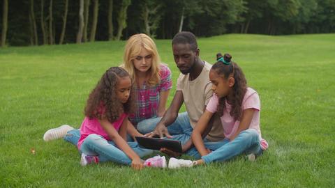 Diverse family with daughters using tablet pc outdoor Acción en vivo