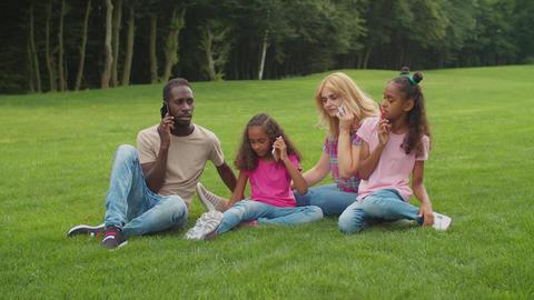 Multiethnic family busy with smart phones outdoors Acción en vivo