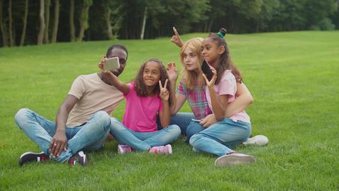 Diverse family with girls taking selfie in park Acción en vivo