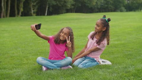 Two cute african sisters making selfie in nature Acción en vivo