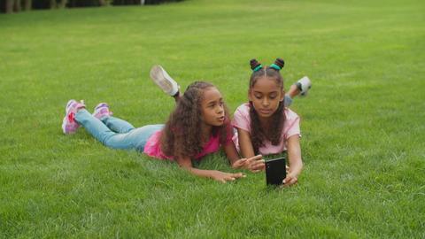 Sisters video conferencing online lying on grass Acción en vivo
