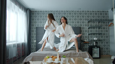 Playful young people in bathrobes dancing on bed, guy is pretenting to play the Live Action