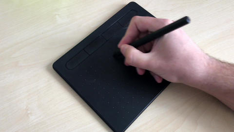 Close-up. Male hands draw with a pen on a graphics tablet. Graphic designer Live Action