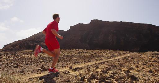 Running man - male runner on desert road running fast in red running clothing Acción en vivo