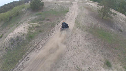 FPV drone is flying over a man on an ATV, off-road racing, high speed Live Action