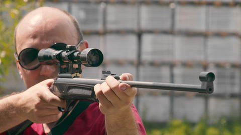 Close up of the face of a man aiming while looking into an optical rifle sight Live Action