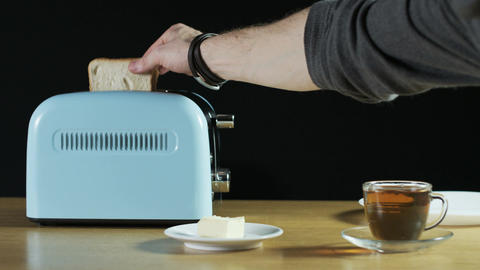 Man Takes Loaves of Bread Out of an Electric Toaster Footage