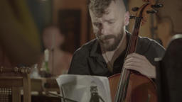 A man plays the cello in front of the audience in the café Footage