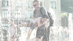 Father playing with his son in the fountain on a Sunny day. Slow motion Footage