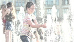 The child plays with the water jets in the fountain during the day. Summer Footage