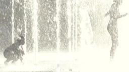 Children playing in the fountain in summer . Slow motion Footage