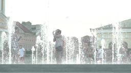 Children play with water jets in the fountain during the day. Summer Footage