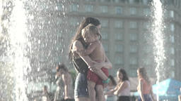 Mother with child on hands near the fountain . Slow motion Footage