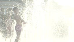 Childhood. Girl playing with water in the fountain . Slow motion Footage