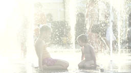Boy and girl with splashes of water in the fountain . Slow motion Footage