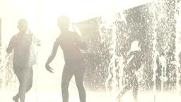 Children play with water jets in the fountain Footage
