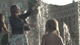 Girl stretches hand to the water jets in the fountain Footage