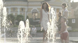 Children in summer having fun in the fountain . Slow motion Footage