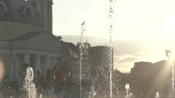 People near the fountain in the evening, in the summer at sunset . Slow motion Footage