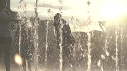 People in the fountain in the summer at sunset . Slow motion Footage