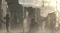 Children playing in the fountain at sunset . Summer. Slow motion Footage