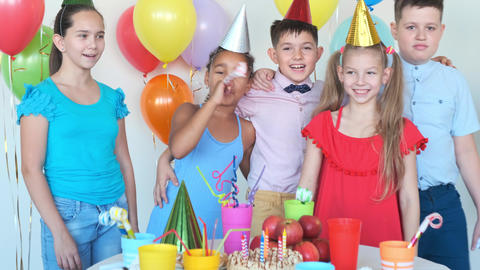 African-American girl blows horn at birthday with friends Live Action