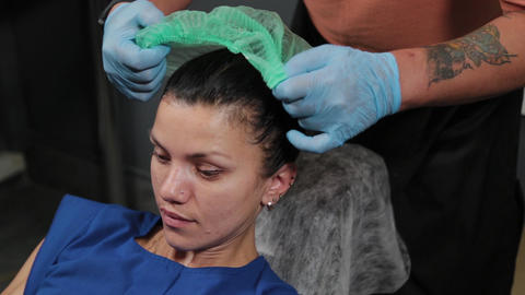 A beautiful woman wears a cap for a procedure in a beauty salon Live Action