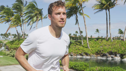 Running Man. Slow motion video of handsome young man jogging in park. Determined Live Action