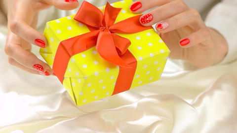 Gift box in beautiful hands slow motion young woman hands with romantic nail design Live Action