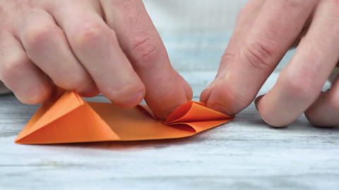 Hands folding origami from orange paper japanese paper Live Action