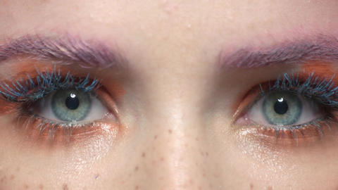 Eyes of woman wide open colorful eye makeup macro Live Action