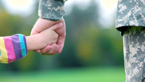 Hands of father and child holding hands of military soldier Live Action