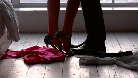 Legs of couple standing indoors clothes lying on the floor Live Action