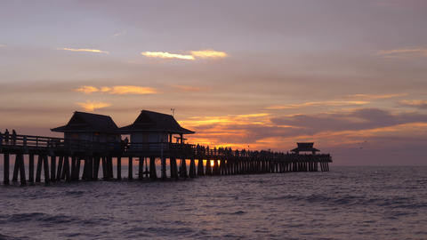 Dark silhouette of a pier over the water at sunset Live Action