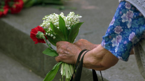 Very old lady with flowers at memorial day Live Action