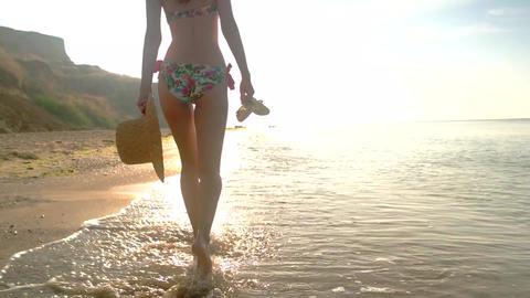 Woman in bikini walking outdoor lady carrying hat near sea shore Live Action