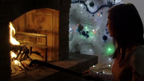 woman managing with a fire hook with a burning fire, christmas time Footage