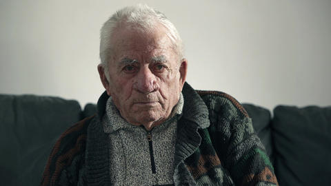 Pensive pensioner on the sofa while look intensly the camera Live Action