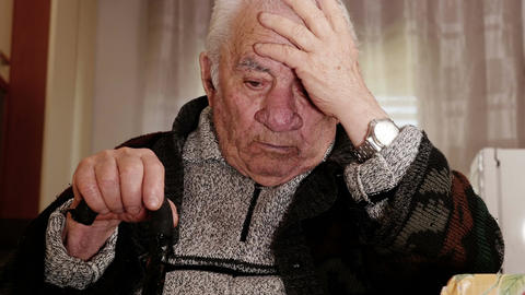 Pensive grandfather rested to his chin, thinking holding his headwith a hand Footage